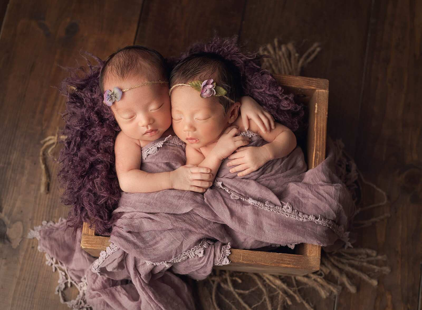 twin girls posed together in a crate with purple wrap and layer